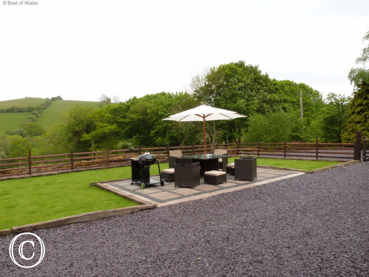 Large lawn and patio with table and chairs & BBQ facilities