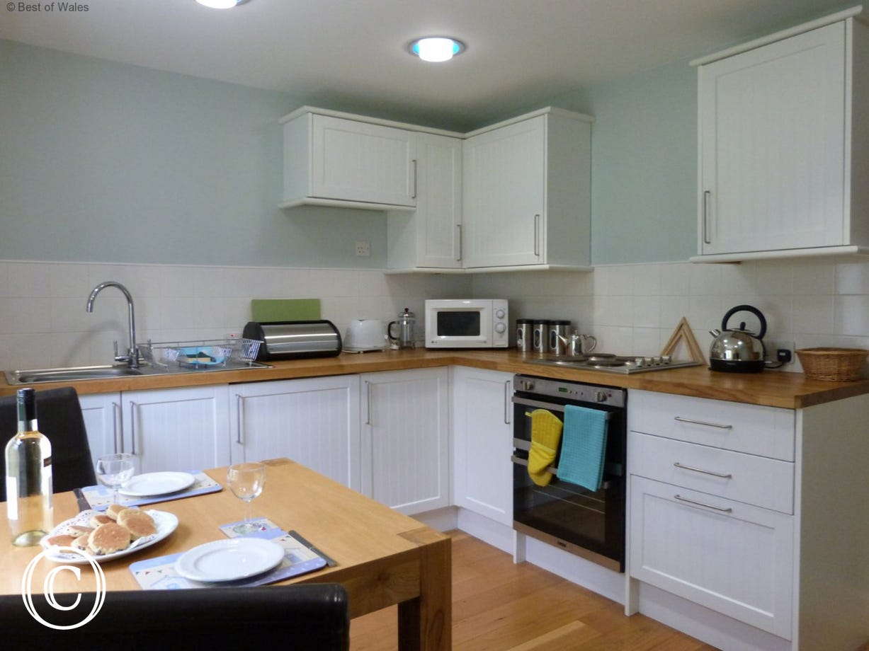 Kitchen includes an electric oven and hob, microwave and fridge