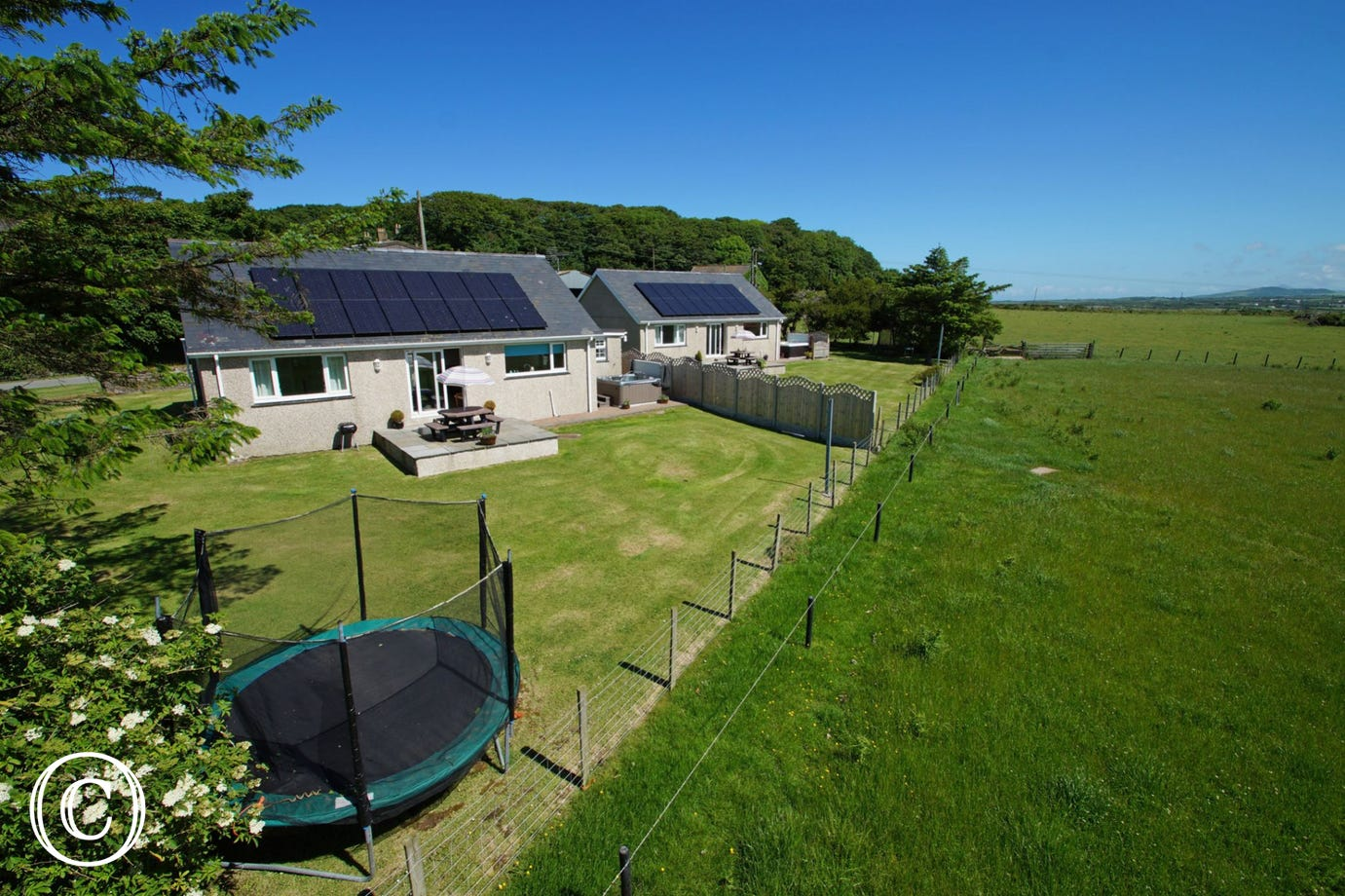 Min y Môr (nearest) is one of two 5 star holiday cottages on site, each with its own enclosed garden and hot tub - ideal for extended family or friends