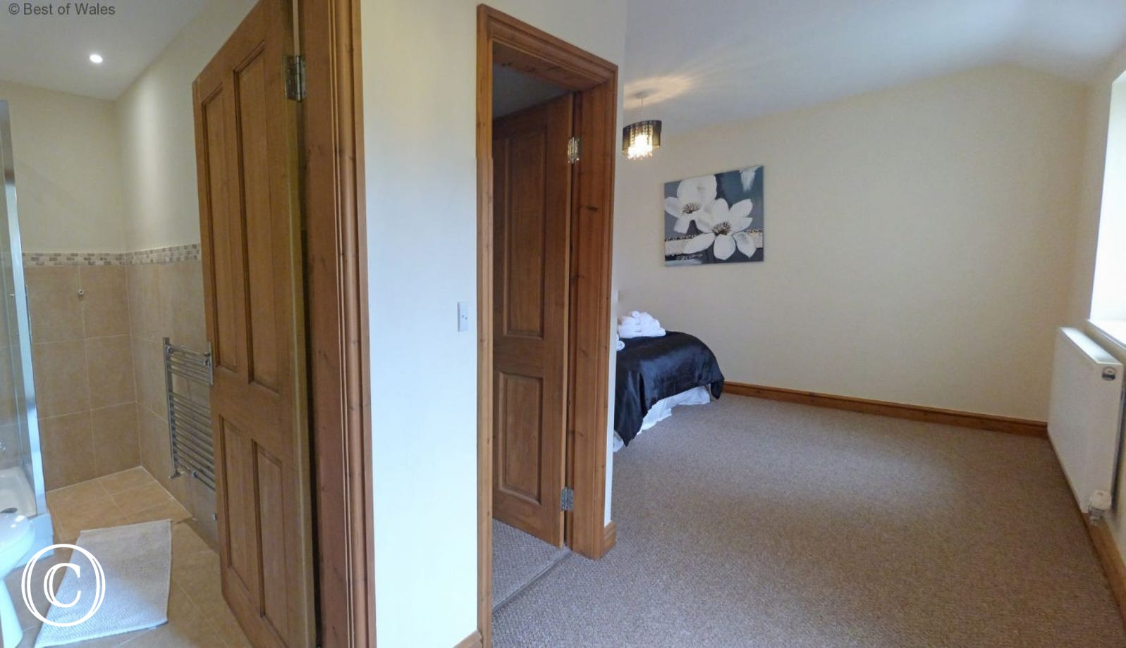 En suite facilities comprising enclosed shower cubicle, WC and wash basin.