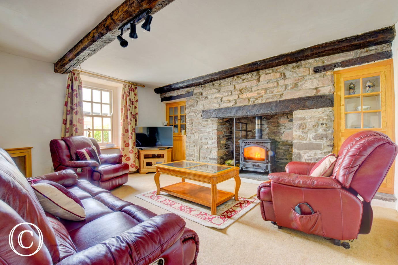 Wood burning stove within traditional feature fireplace.