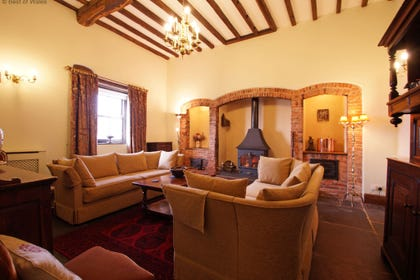 Spacious lounge with welcoming woodburner, rugs and large comfy sofas