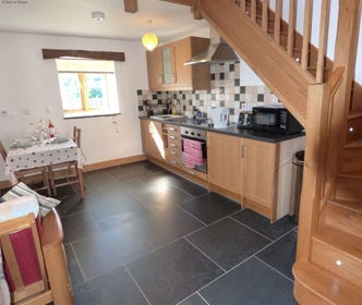 Kitchen/diner with slate flooring and light modern fitted kitchen
